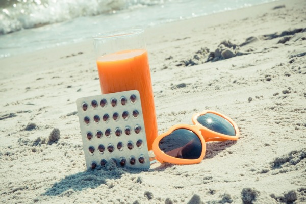 Vintage photo, Medical pills, carrot juice and sunglasses on sand at beach, concept of prevention of vitamin A deficiency, beautiful and lasting tan