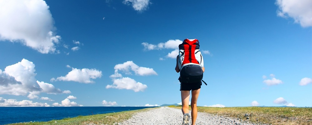Backpacker walking on road under blue sky with clouds